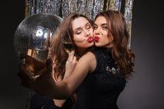 2 счастливых женщины посылая поцелуи и выпивая шампанское Стоковая Фотография