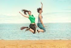 2 счастливых женщины при веник скача на пляж Стоковые Фото