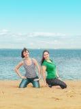 2 счастливых женщины сидя на пляже Стоковые Фотографии RF