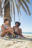 2 счастливых женщины сидя на смеяться над пляжа Стоковые Фото