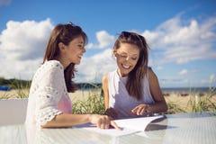 2 счастливых женщины сидя на таблице кафа на меню чтения пляжа Стоковое фото RF