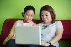 2 счастливых женщины смотря компьтер-книжку пока лежащ Стоковое Изображение