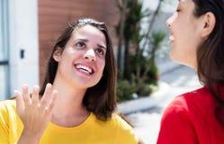 2 счастливых кавказских девушки говоря в городе Стоковая Фотография RF