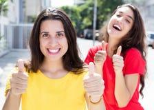 2 счастливых кавказских девушки показывая большие пальцы руки вверх Стоковое Фото