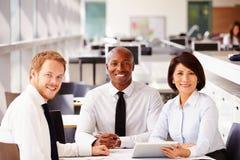 3 счастливых коллеги офиса смотря к камере Стоковые Изображения RF