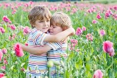 2 счастливых маленьких белокурых дет в зацветая маке Стоковое Изображение