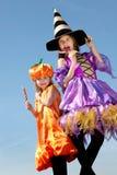2 счастливых маленьких девушки хеллоуина лижа конфеты Стоковое фото RF