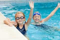 2 счастливых маленькой девочки играя в бассейне Стоковые Изображения RF