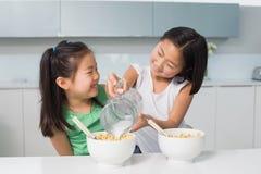 2 счастливых маленькой девочки лить молоко в шаре в кухне Стоковое Изображение