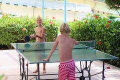 2 счастливых мальчика играя пингпонг outdoors Стоковая Фотография RF