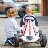 2 счастливых мальчика отпрыска играя с автомобилем игрушки Стоковые Изображения