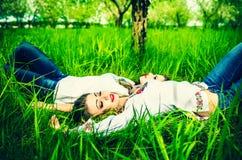2 счастливых милых девушки лежа на зеленой траве Стоковое фото RF