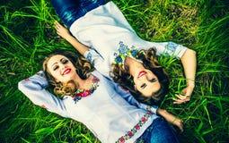 2 счастливых милых девушки лежа на зеленой траве Стоковое Изображение