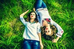 2 счастливых милых девушки лежа на зеленой траве Стоковая Фотография