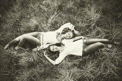 2 счастливых милых девушки лежа на траве Стоковые Изображения RF