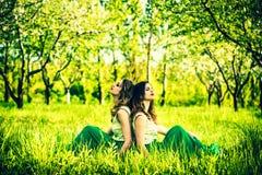 2 счастливых милых девушки сидя на зеленой траве Стоковая Фотография