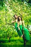 2 счастливых милых девушки сидя на яблоне цветения Стоковое Фото