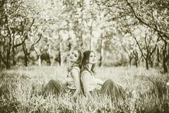 2 счастливых милых девушки сидя на яблоне цветения Стоковые Фото