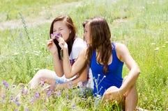 2 счастливых милых друз играя с цветками внутри Стоковая Фотография