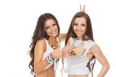 2 счастливых модных молодой женщины показывая большие пальцы руки вверх нося красочные ювелирные изделия Стоковое фото RF