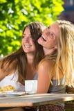 2 счастливых молодой женщины в кафе улицы Стоковая Фотография RF