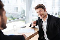 2 счастливых молодых бизнесмена говоря в офисе Стоковые Фотографии RF