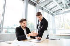 2 счастливых молодых бизнесмена говоря и используя компьтер-книжку Стоковое фото RF