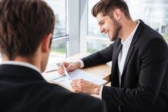 2 счастливых молодых бизнесмена обсуждая бизнес-план совместно Стоковое Изображение