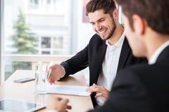 2 счастливых молодых бизнесмена сидя и работая с документами совместно Стоковое Изображение