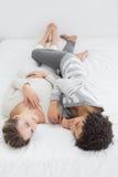 2 счастливых молодых женских друз лежа в кровати Стоковое Фото