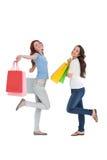 2 счастливых молодых женских друз с хозяйственными сумками Стоковое Изображение
