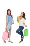 2 счастливых молодых женских друз с хозяйственными сумками Стоковое фото RF