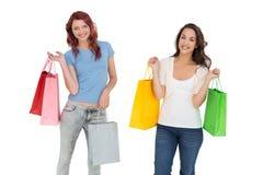 2 счастливых молодых женских друз с хозяйственными сумками Стоковые Фотографии RF