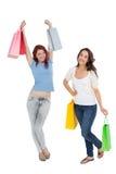 2 счастливых молодых женских друз с хозяйственными сумками Стоковая Фотография