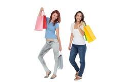 2 счастливых молодых женских друз с хозяйственными сумками Стоковые Изображения RF