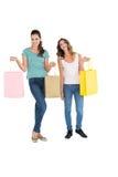 2 счастливых молодых женских друз с хозяйственными сумками Стоковые Фото