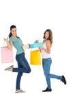 2 счастливых молодых женских друз с хозяйственными сумками Стоковое Фото