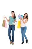 2 счастливых молодых женских друз с хозяйственными сумками Стоковые Изображения