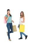 2 счастливых молодых женских друз с хозяйственными сумками Стоковая Фотография RF