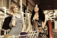 2 счастливых молодых женщины моды с магазинной тележкаой в моле Стоковые Изображения RF