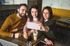 3 счастливых молодых друз принимая selfie с smartphone в кафе Стоковое фото RF