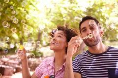 2 счастливых молодых друз дуя пузыри стоковые изображения rf