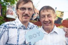 2 счастливых обнимая усмехаясь старших люд с мальчиком подписывают положение совместно во время вечеринки по случаю дня рождения Стоковое Изображение