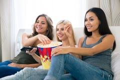 3 счастливых подруги есть попкорн и смотря ТВ Стоковое Изображение