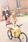 2 счастливых подруги ехать тандемный велосипед Стоковое Фото