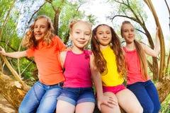 4 счастливых подруги сидя на упаденном дереве Стоковые Изображения
