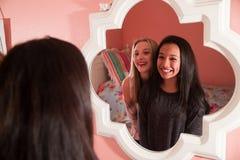 2 счастливых предназначенных для подростков девушки смотря в зеркале Стоковое Изображение