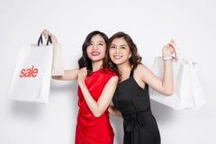 2 счастливых привлекательных молодой женщины с хозяйственными сумками на белом bac Стоковое Изображение RF