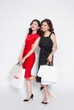 2 счастливых привлекательных молодой женщины с хозяйственными сумками на белом bac Стоковое фото RF