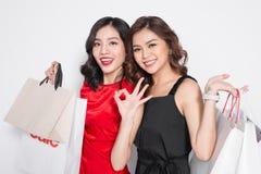 2 счастливых привлекательных молодой женщины с хозяйственными сумками на белом bac Стоковые Изображения